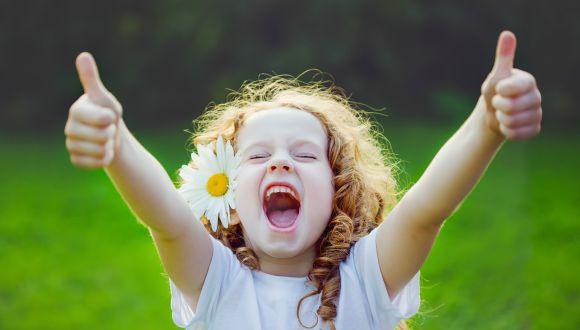ילדה מרימה אגודלים בשמחה