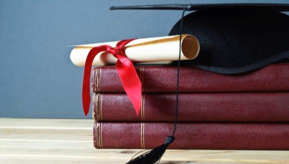 תעודה וכובע סיום על גבי ספרים