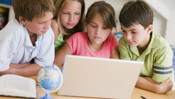 קבוצת ילדים מתבוננת בלפ-טופ