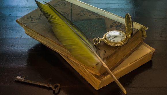 נוצה ושעון כיס מונחים על ספרים